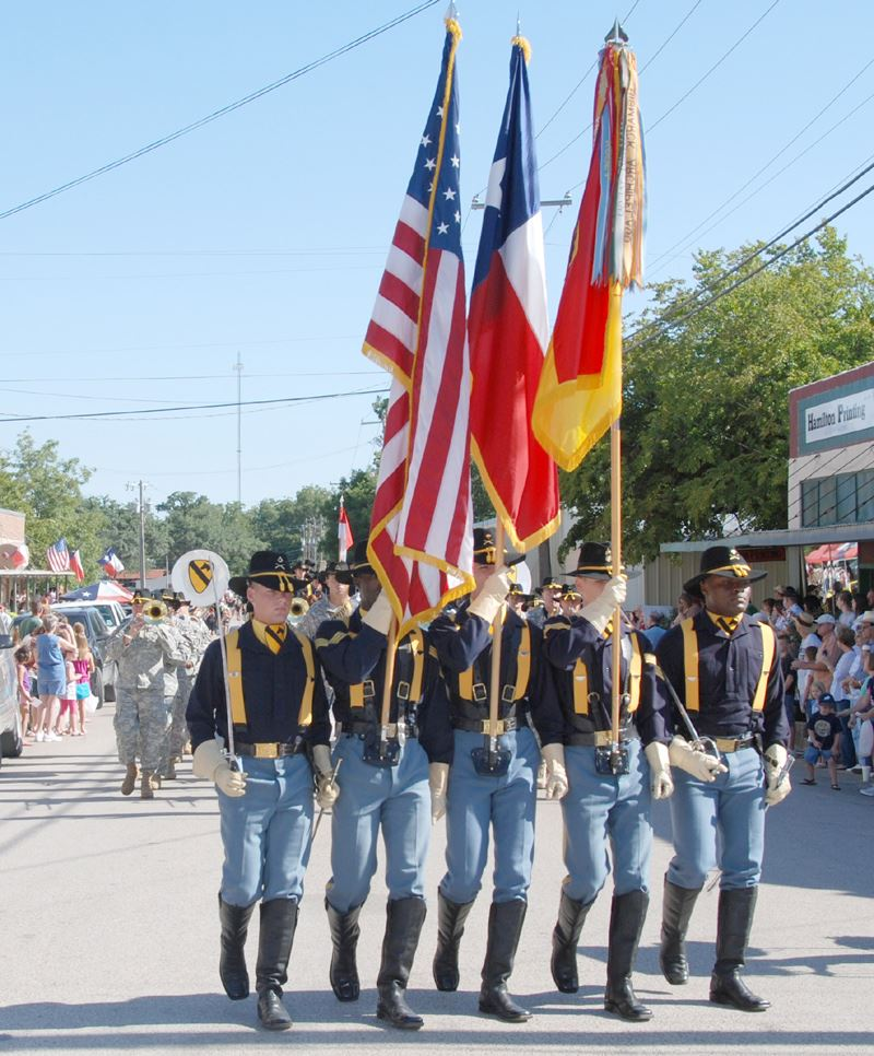 Calvary men carrying flags during a parade