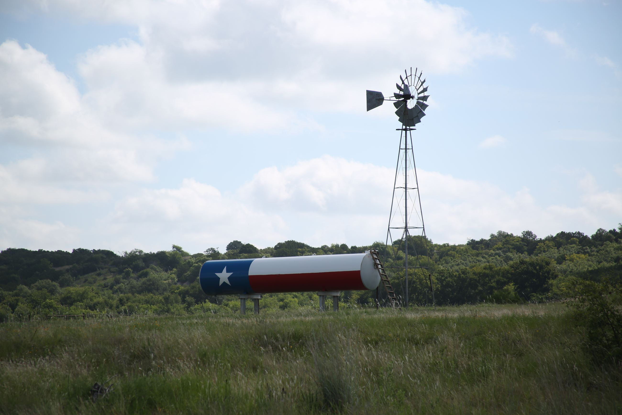 Windmill next to a Texas flag painted tank