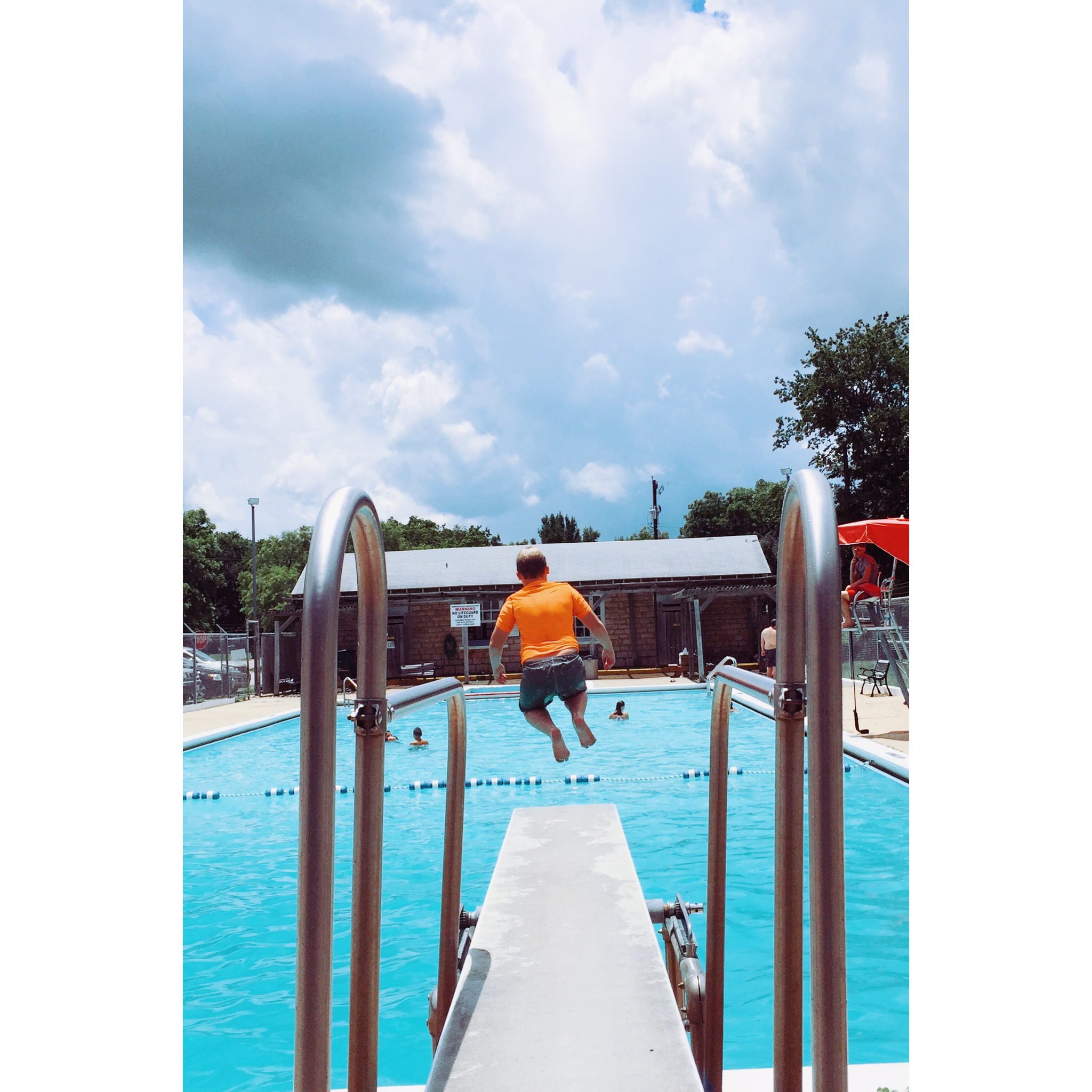 Boy jumping off the diving board into the pool